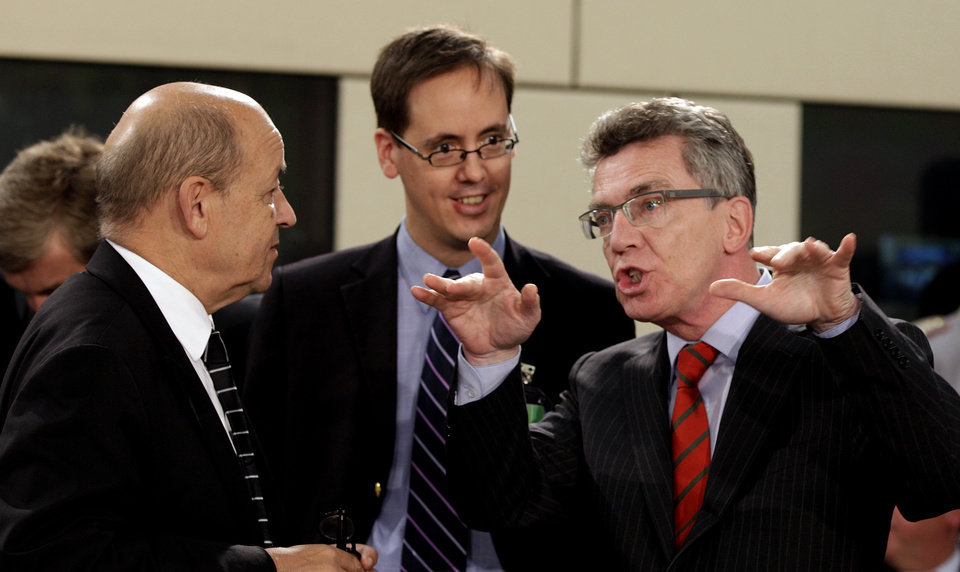 Photo -   German Defense Minister Thomas de Maiziere, right, speaks with French Defense Minister Jean-Yves Le Drian, left, during a meeting of NATO Defense Ministers at NATO headquarters in Brussels on Tuesday, Oct. 9, 2012. NATO defense leaders gathering for a two-day meeting in Brussels, are committed to the war in Afghanistan, according to U.S. and alliance officials, but there are growing signs that the Afghan political and military hostilities against the coalition are starting to wear on the coalition. (AP Photo/Virginia Mayo)