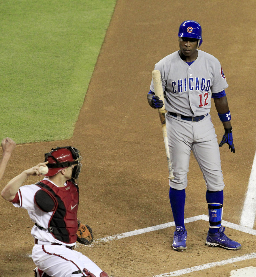 Photo -   Chicago Cubs' Alfonso Soriano (12) pauses in the batter's box after being called out on strikes as Arizona Diamondbacks' Miguel Montero throws the ball back to the infield during the first inning in a baseball game Friday, June 22, 2012, in Phoenix. (AP Photo/Ross D. Franklin)