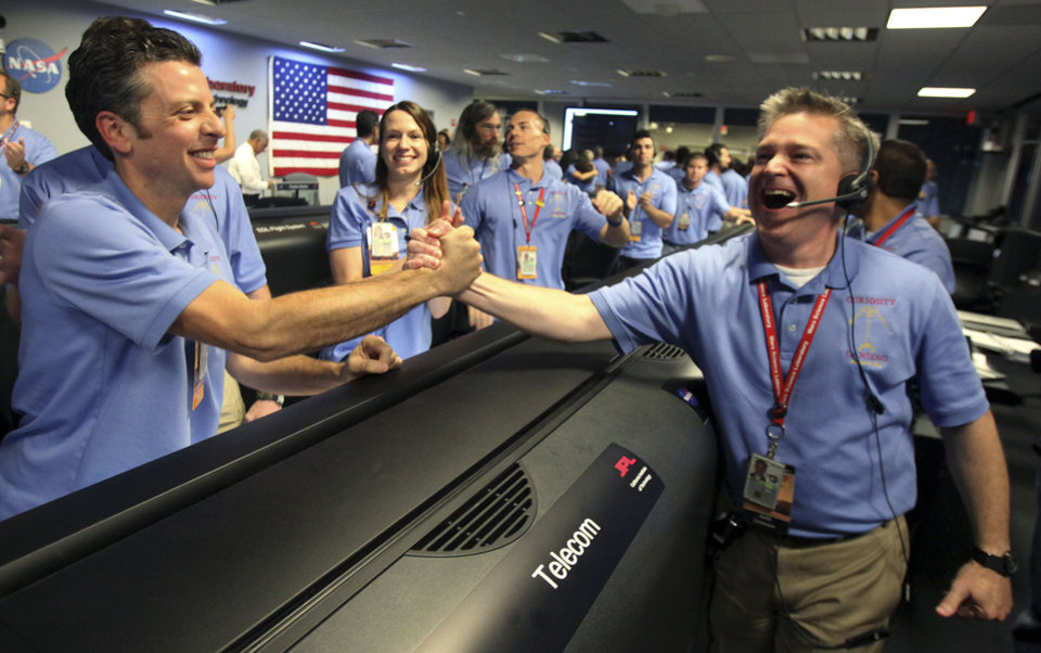 Photo -   Flight director Keith Comeaux, right, celebrates with Martin Greco after a successful landing inside the Spaceflight Operations Facility for NASA's Mars Science Laboratory Curiosity rover at Jet Propulsion Laboratory in Pasadena, Calif., Sunday, Aug. 5, 2012. The Curiosity robot is equipped with a nuclear-powered lab capable of vaporizing rocks and ingesting soil, measuring habitability, and potentially paving the way for human exploration. (AP Photo/Brian van der Brug,Pool)