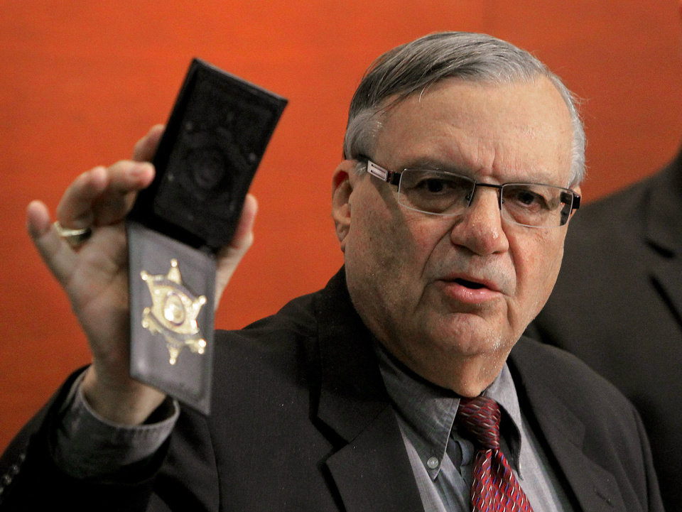 Photo - Maricopa County Sheriff Joe Arpaio shows his badge as he holds a ceremony where 92 of his immigration jail officers, who lost their federal power to check whether inmates are in the county illegally, turn in their credentials after federal officials pulled the Sheriff's office immigration enforcement powers Wednesday, Dec. 21, 2011, in Phoenix.  The U.S. Department of Homeland Security stripped Sheriff Joe Arpaio's jail officers of their federal powers after federal authorities accused the sheriff's office last week of a wide range of civil rights violations. (AP Photo/Ross D. Franklin)