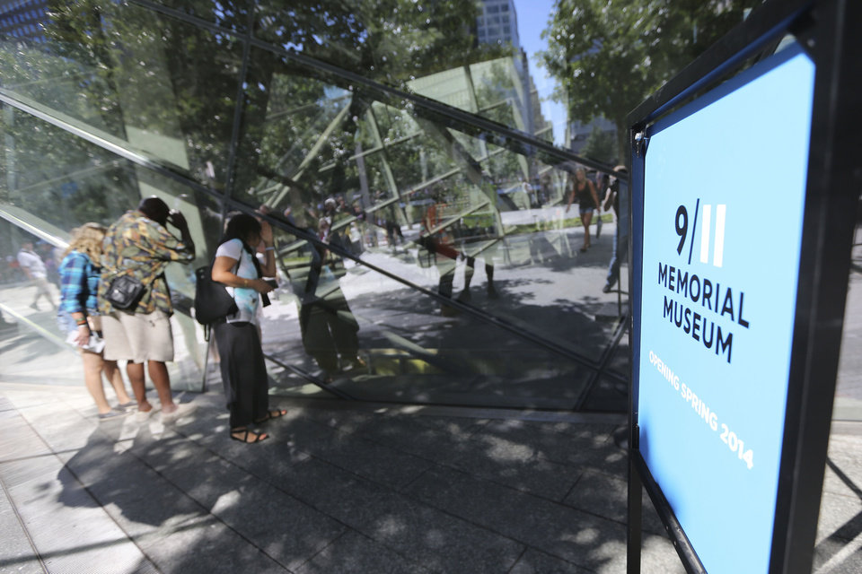 Photo - Visitors to the National September 11 Memorial and Museum peak into the museum, Friday, Sept. 6, 2013 in New York. Construction is racing ahead inside the museum as the 12th anniversary of the Sept. 11, 2001 attacks draws near. Several more large artifacts have been installed in the cavernous space below the World Trade Center memorial plaza. (AP Photo/Mary Altaffer)