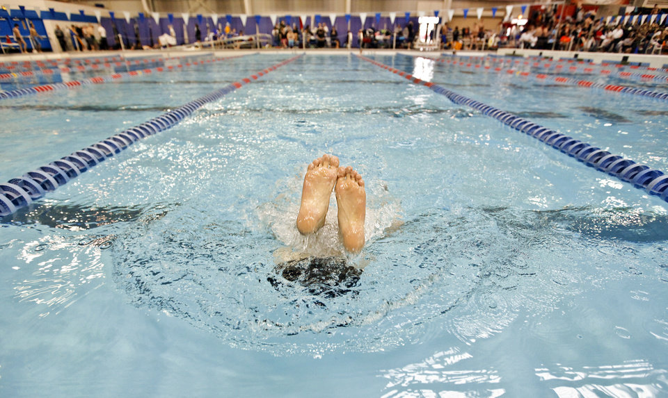A competitor's feet stays above the water while turning on the wall in warm ups during the OSSAA class 5A state championship swim meet at the Oklahoma City Community College on Friday, Feb. 17, 2012, in Oklahoma City, Okla. Photo by Chris Landsberger, The Oklahoman