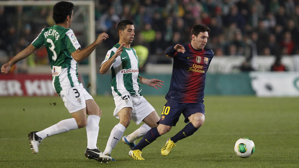 Barcelona's Lionel Messi from Argentina, right, and Cordoba's Carlos Caballero, center, vie for the ball during the 1st leg of a last-16 Copa del Rey soccer match at Arcangel stadium in, Cordoba, Spain on Wednesday, Dec. 12, 2012. (AP Photo/Angel Fernandez)