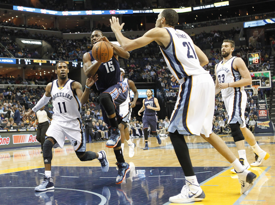 Photo - Charlotte Bobcats guard Kemba Walker (15) drives to the basket against Memphis Grizzlies defenders Mike Conley (11), Tayshaun Prince (21) and Marc Gasol (33), of Spain, in the first half of an NBA basketball game Saturday, March 8, 2014, in Memphis, Tenn. (AP Photo/Lance Murphey)