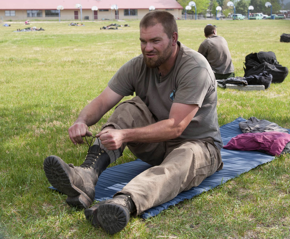Photo -   Doug Denlinger from the Smith River Hotshots in N. Calif., puts his boots on after resting at White Mountain Academy in Eager, Ariz., while fighting a wildfire, Sunday, June 5, 2011. (AP Photo/The Arizona Republic, Michael Chow)