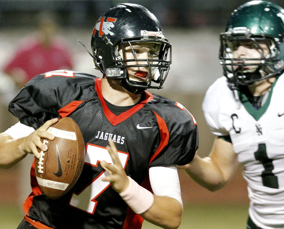Photo - Norman North's Daniel Davis chases  Westmoore QB Trevor Thompson during their game at Moore's stadium in Moore, Okla., on Thursday, Sept. 16, 2010. Photo by John Clanton, The Oklahoman