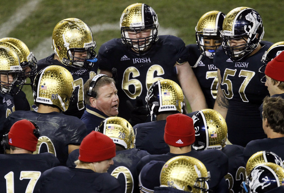 FILE - In this Oct. 6, 2012, file photo, Notre Dame head coach Brian Kelly, center left, talks to his team during the second half of an NCAA college football game against Miami at Soldier Field in Chicago. About the only thing the Irish haven�t done yet this season is rally from behind to win. The Irish have been able to ignore what coach Kelly refers to as the �noise� so far, but it keeps getting louder with every victory.(AP Photo/Charles Rex Arbogast, File)