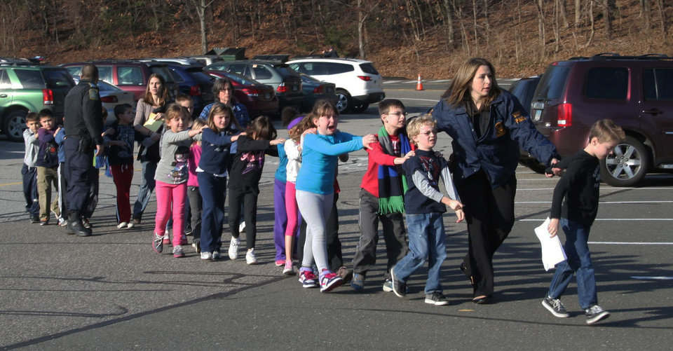 Photo - FILE - In this Friday, Dec. 14, 2012 file photo provided by the Newtown Bee, Connecticut State Police lead a line of children from the Sandy Hook Elementary School in Newtown, Conn. after a shooting at the school. The private equity firm Cerberus will sell its stake in a firearms company that produced one of the weapons believed to have been used in the shootings at the elementary school, calling it a