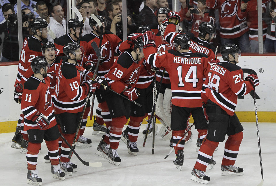 Photo -   New Jersey Devils' Travis Zajac (19) is congratulated by teammates after his overtime goal in Game 6 of a first-round NHL hockey Stanley Cup playoff series against the Florida Panthers, Tuesday, April 24, 2012, in Newark, N.J. The Devils won 3-2, sending the series to a seventh game. (AP Photo/Julio Cortez)