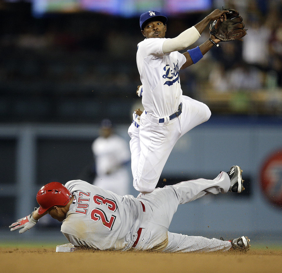 Photo - Los Angeles Dodgers second baseman Dee Gordon, top, throws to first base after forcing out Cincinnati Reds' Donald Lutz during the seventh inning of a baseball game on Tuesday, May 27, 2014, in Los Angeles. Cincinnati Reds' Zack Cozart was safe at first. (AP Photo/Jae C. Hong)