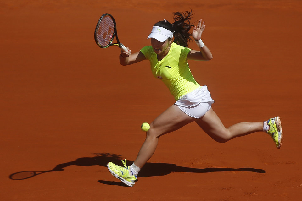 Photo - Jie Zheng from China serves during a Madrid Open tennis tournament match against Na Li from China, in Madrid, Spain, Tuesday May 6, 2014. (AP Photo/Andres Kudacki)
