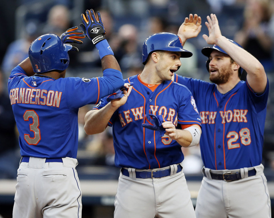 Photo - New York Mets Curtis Granderson celebrates with David Wright, center, and Daniel Murphy after Granderson hit a first-inning, three-run, home run in a baseball game at Yankee Stadium in New York, Tuesday, May 13, 2014.  (AP Photo)