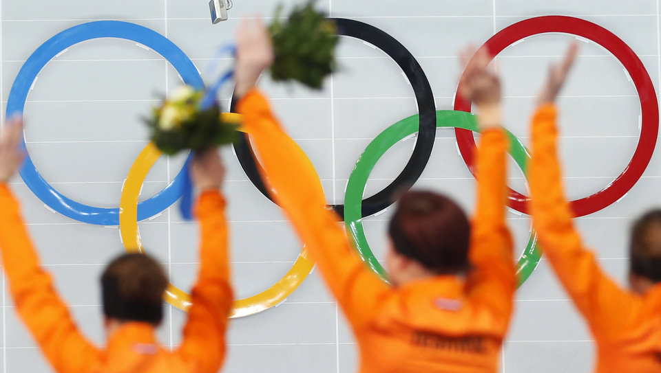 Photo - Athletes from the Netherlands, from left to right, silver medallist Ireen Wust, Gold medallist Jorien ter Mors and bronze medallist Lotte van Beek celebrate during the flower ceremony for the women's 1,500-meter speedskating race at the Adler Arena Skating Center during the 2014 Winter Olympics in Sochi, Russia, Sunday, Feb. 16, 2014.  (AP Photo/Pavel Golovkin)