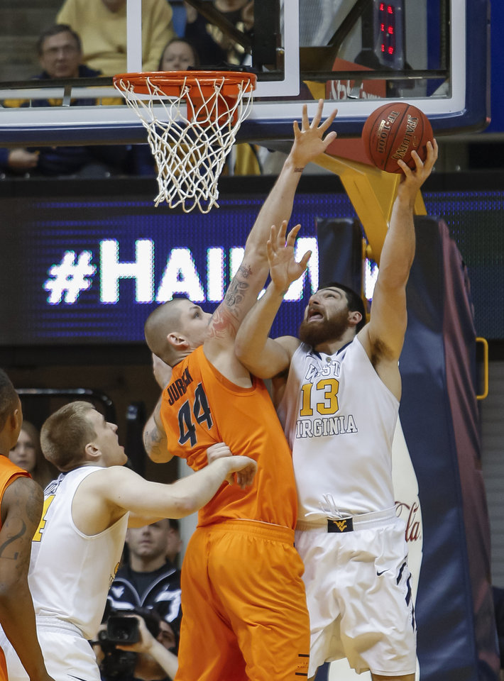 Photo - West Virginia's Deniz Kilicli (13) shoots over Oklahoma State's Philip Jurick during the first half of an NCAA college basketball game in Morgantown, W.Va., on Saturday, Feb. 23, 2013. (AP Photo/David Smith)