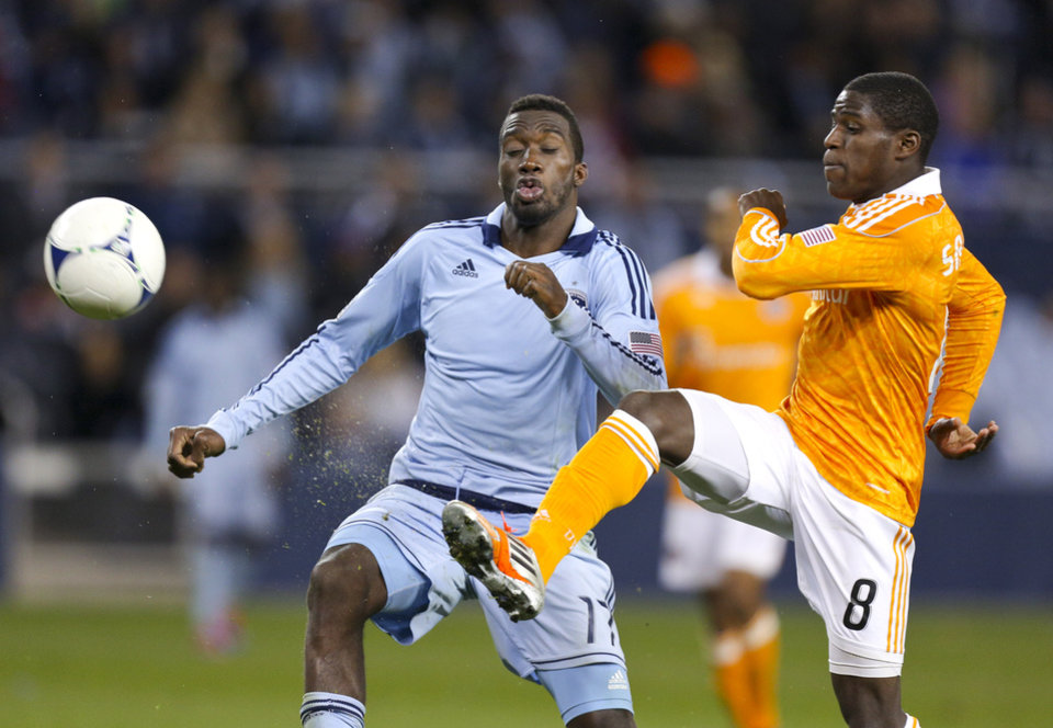 Photo -   Houston Dynamo's Kofi Sarkodie (8) clears the ball against Sporting Kansas City's C.J. Sapong during the second half of an MLS soccer playoff game Wednesday, Nov. 7, 2012, in Kansas City, Kan. (AP Photo/Ed Zurga)