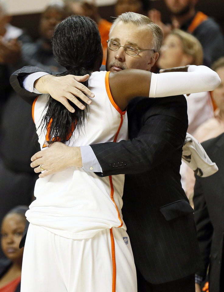 Photo - OSU head coach Jim Littell hugs Toni Young (15) as she leaves the game late in the second half during the Bedlam women's college basketball game between Oklahoma State University and the University of Oklahoma at Gallagher-Iba Arena in Stillwater, Okla., Saturday, Feb. 23, 2013. OSU beat OU, 83-62. Photo by Nate Billings, The Oklahoman