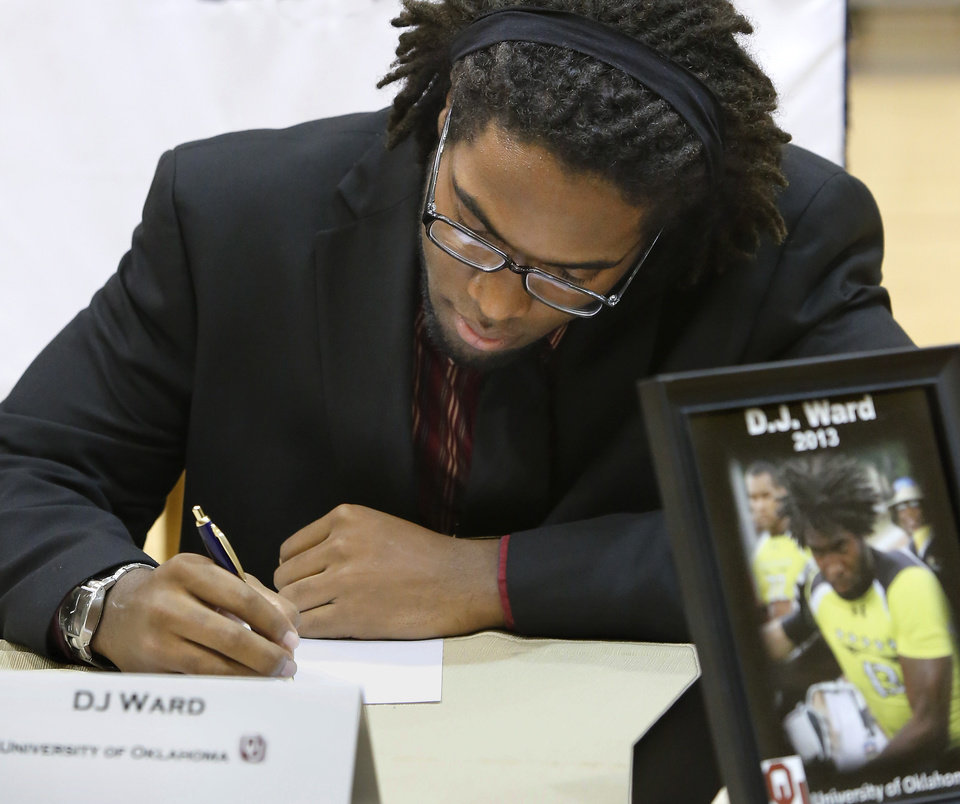 Photo - D. J. Ward signs a letter of intent to play football at the University of Oklahoma.  More than a dozen Southmoore High School athletes signed letters of intent to play at various colleges and universities  during an afternoon signing ceremony  in the school's gymnasium on Wednesday, Feb. 6, 2013.  Photo by Jim Beckel, The Oklahoman