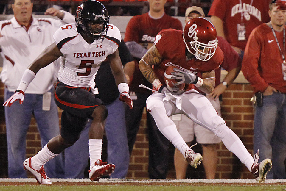 Photo - Oklahoma's Kenny Stills (4) scores a touchdown in front of Texas Tech's Tre' Porter (5) during the college football game between the University of Oklahoma Sooners (OU) and Texas Tech University Red Raiders (TTU) at the Gaylord Family-Oklahoma Memorial Stadium on Saturday, Oct. 22, 2011. in Norman, Okla. Photo by Chris Landsberger, The Oklahoman