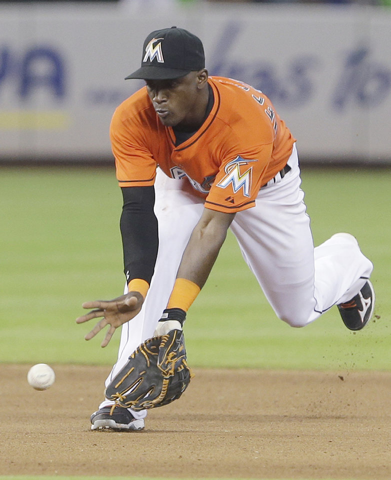 Photo - Miami Marlins shortstop Adeiny Hechavarria fields a ball hit by Los Angeles Dodgers' Carl Crawford during the fourth inning of a baseball game on Sunday, May 4, 2014, in Miami. Crawford was out at first. (AP Photo/Wilfredo Lee)