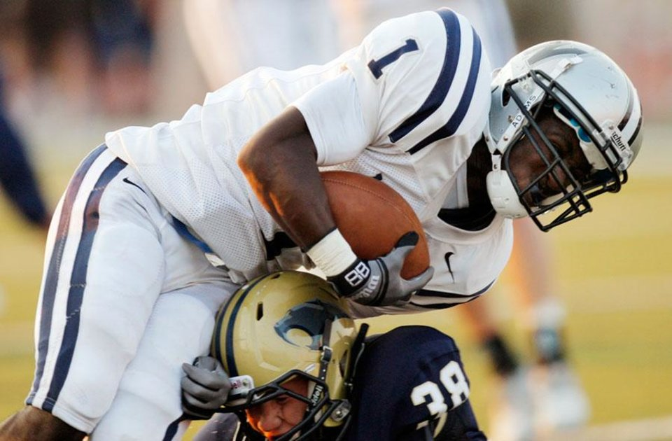 Photo -  Edmond North's Jarion Tudman (1) pushes past Southmoore's Colton Shackelford (38) for a touchdown during a high school football game between Edmond North and Southmoore in Moore, Okla., Thursday, Sept. 1, 2011. Photo by Nate Billings, The Oklahoman