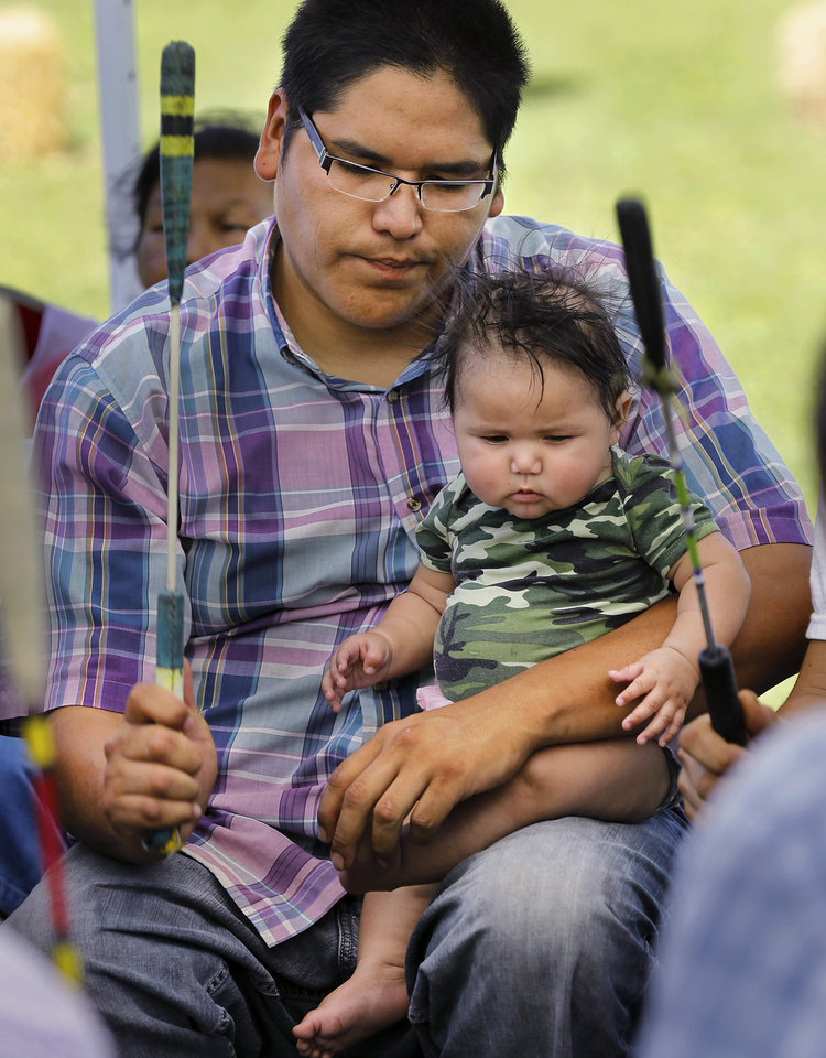 Photo -  James Redbird, of El Reno, lets his 6-month-old daughter Amylah Redbird sit on his lap while he provides dance music with a group of drummers and singers at Joe B. Barnes Regional Park in Midwest City. Photo by Jim Beckel, The Oklahoman   Jim Beckel -