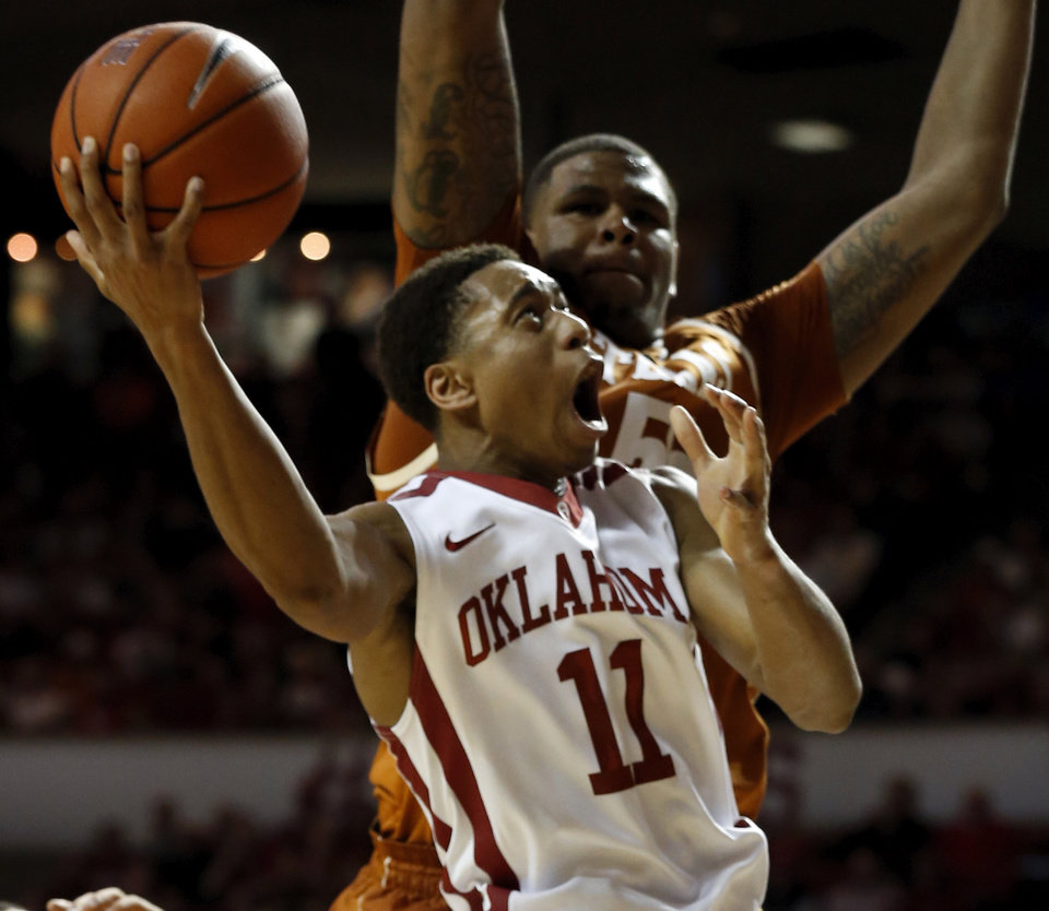 OU�s Isaiah Cousins shoots past Texas� Cameron Ridley during Saturday�s matchup.
