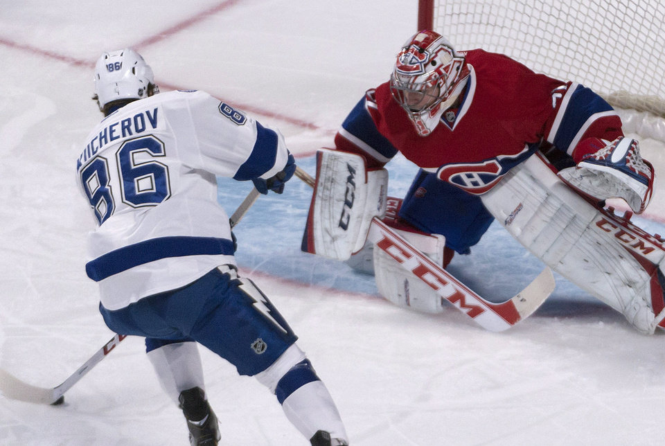 Photo - Montreal Canadiens goalie Carey Price eyes the puck as Tampa Bay Lightning Nikita Kucherov, of Russia, tries to score during a penalty shot in first period of an NHL game in Montreal Saturday, Feb. 1, 2014. (AP Photo/The Canadian Press, Peter McCabe)
