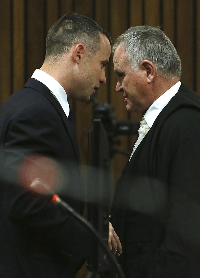 Photo - Oscar Pistorius, right, and his defense attorney Barry Roux, left, attend his murder trial at a court in Pretoria, South Africa, Tuesday May 6, 2014. Pistorius is charged with the shooting death of his girlfriend Reeva Steenkamp on Valentine's Day in 2013. (AP Photo/Alon Skuy, Pool)
