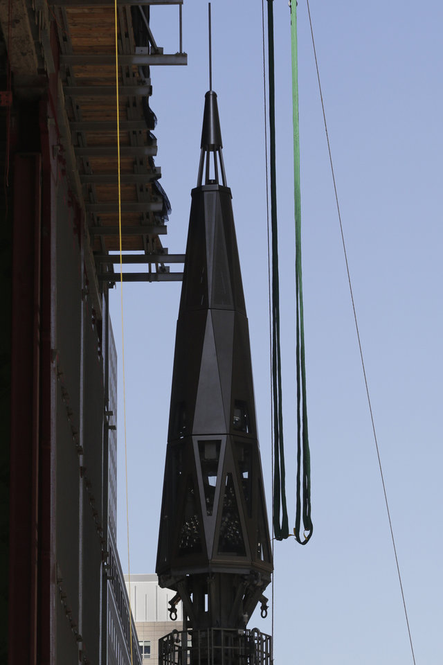 Photo - A harness is lowered to the final piece of spire before it is hoisted to the roof of One World Trade Center, Thursday, May 2, 2013 in New York.  The piece will be attached to the spire at a later date, capping off the tower at 1,776 feet. (AP Photo/Mark Lennihan)