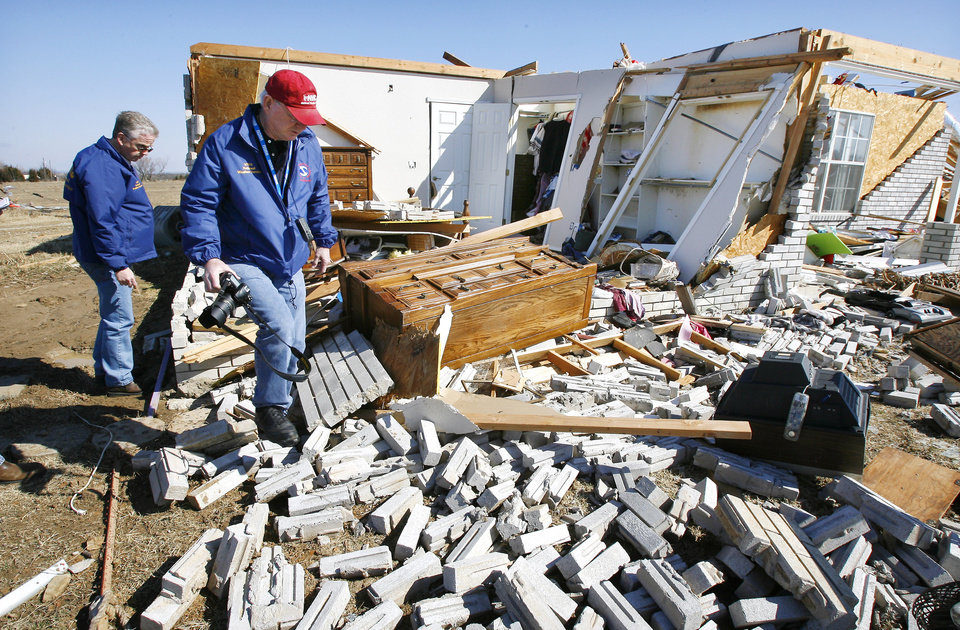 Photo - Rick Smith, warning coordination meteorologist, and Mike Foster, meteorologist in charge, both with the National Weather Service Forecast Office, Norman, looking at house damage to rate the tornado intensity on Brock Road in Lone Grove, Wednesday, Feb. 11, 2009.  BY PAUL B. SOUTHERLAND, THE OKLAHOMAN