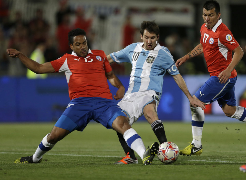 Photo -   Argentina's Lionel Messi vies for the ball with Chile's Jean Beausejour, left, as Chile's Gary Medel, right, looks on during a World Cup 2014 qualifying soccer match in Santiago, Chile, Tuesday, Oct. 16, 2012. (AP Photo/Eduardo Di Baia)