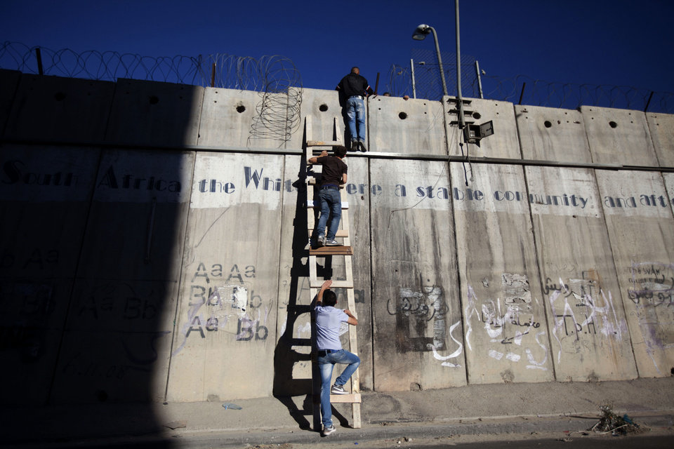 Photo - Palestinians use a ladder to climb over the separation barrier with Israel on their way to pray at the al-Aqsa Mosque in Jerusalem during the Muslim holy month of Ramadan, in Al-Ram, north of Jerusalem, Friday, July 11, 2014. (AP Photo/Majdi Mohammed)