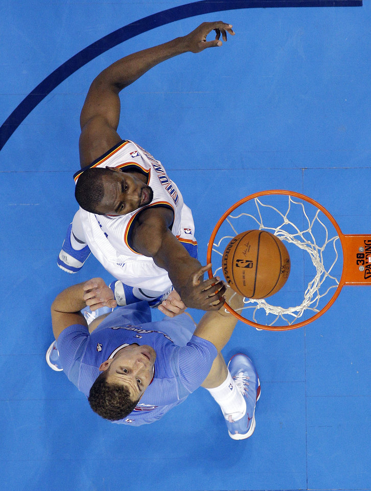 Photo - Oklahoma City 's Serge Ibaka (9) dunks over Los Angeles' Blake Griffin (32) during the NBA game between the Oklahoma City Thunder and the Los  Angeles Clippers at the Chesapeake Energy Arena, Sunday, Feb. 23, 2014. Photo by Sarah Phipps, The Oklahoman