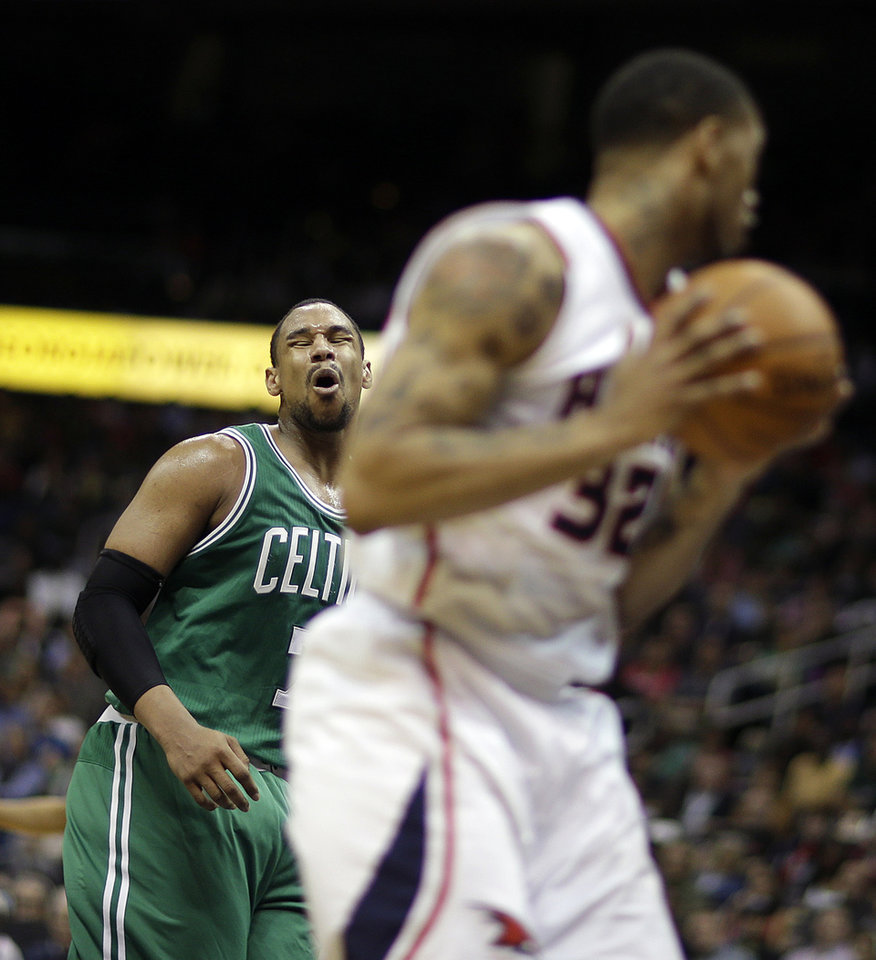 Photo - Boston Celtics' Jared Sullinger, left, reacts after missing a shot as the rebound falls into the hands of Atlanta Hawks' Mike Scott, right, in the third quarter of an NBA basketball game, Wednesday, April 9, 2014, in Atlanta. (AP Photo/David Goldman)