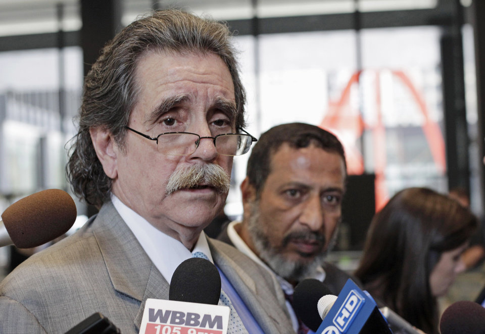 Thomas Durkin, defense attorney for Adel Daoud, 18, of Chicago suburban Hillside, speaks to reporters at the federal building in Chicago, Thursday, Sept. 20, 2012, after a federal grand jury indicted Daoud on charges of attempting to use a weapon of mass destruction and attempting to damage or destroy a building by means of an explosive. Daoud, who turns 19 on Friday, was arrested last week after authorities say he tried to ignite what he thought was a car bomb outside a Chicago bar using a fake mechanism set up by the FBI as a part of a sting. Listening to Durkin is Daoud's father, Ahmed Daoud. (AP Photo/Teresa Crawford)