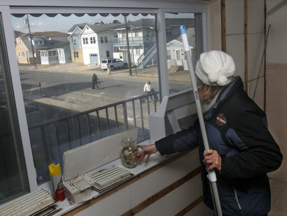 Kim Baker watches as neighbors drag debris to the trash, as she works to clean up her Superstorm Sandy  damaged home in Seaside Heights, N.J., Thursday, Jan. 3, 2013. New Jersey Gov. Chris Christie, a Republican who has praised President Barack Obama's handling of Superstorm Sandy, has blasted U.S. House Speaker John Boehner for delaying a vote for federal storm relief. Under intense pressure from angry Republicans, House Speaker John Boehner has agreed to a vote this week on aid for Superstorm Sandy recovery.    (AP Photo/Mel Evans)