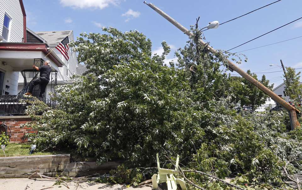 Photo - Homeowner Lenny DiBartolomeo, left, puts his flag back into its holder on his house in Revere, Mass., Monday, July 28, 2014 after a tornado touched down. DiBartolomeo said he was grateful that he knew of no injuries despite the damage to his home. (AP Photo/Elise Amendola)