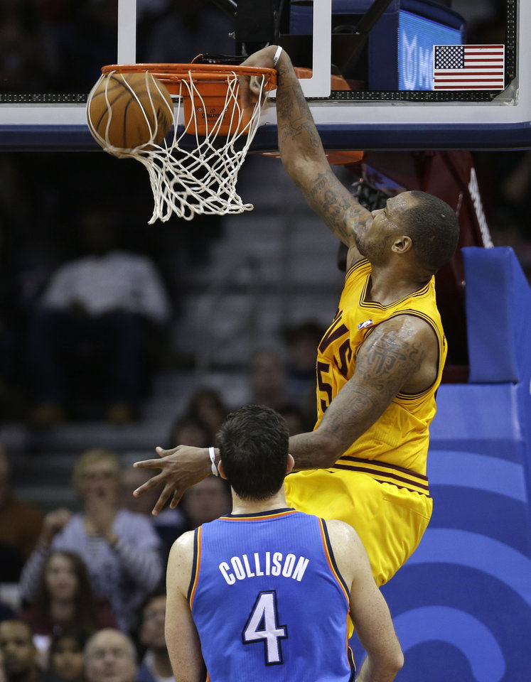 Cleveland Cavalier's Marreese Speights, top, dunks the ball over Oklahoma City Thunder's Nick Collison (4) during the fourth quarter of an NBA basketball game on Saturday, Feb. 2, 2013, in Cleveland. The Cavaliers won 115-110. (AP Photo/Tony Dejak) ORG XMIT: OHTD107