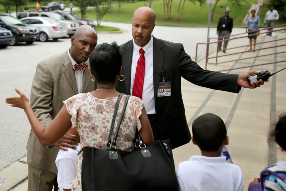 Photo - Ronald E. McNair Discovery Learning Academy assistant principal Johnny Potter, left, and principal Brian Bolden, right, talks with a parent and her children Wednesday, Aug. 21, 2013, a day after an armed suspect cause an ordeal at their school in Decatur, Ga. The learning academy held classes at McNair High School on Wednesday after a gunman on Tuesday held one or two staff members captive and fired into the floor of the school office. As officers swarmed the campus outside, he shot at them at least a half a dozen times with an assault rifle from inside the school and they returned fire, police said. (AP Photo/Atlanta Journal-Constitution, Jason Getz)