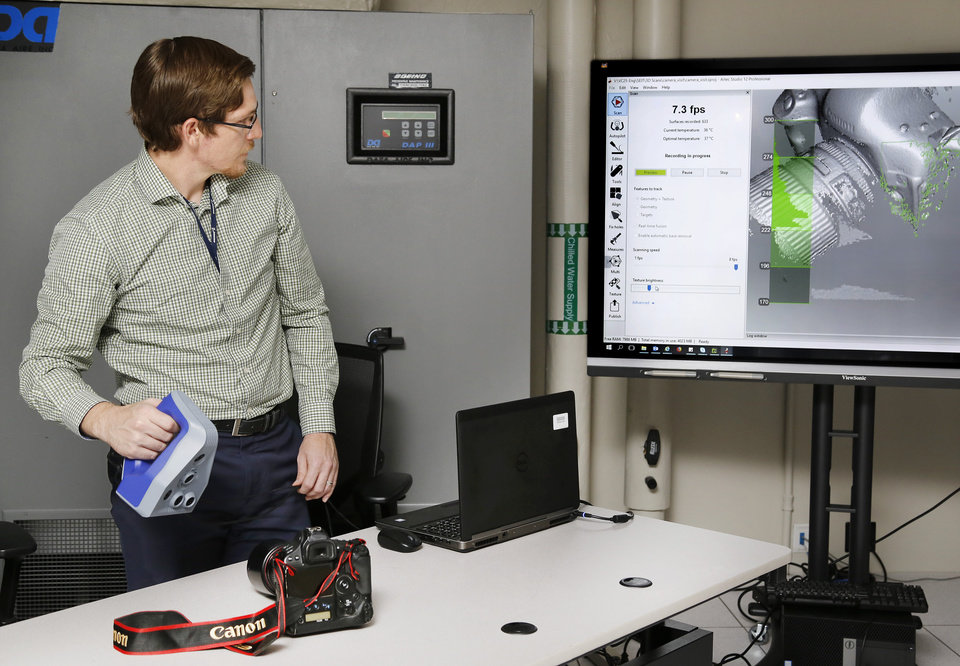 Photo -  Boeing systems engineer Nick Julch uses a light-sensing 3-D scanner to create a digital model of a camera at the company's Virtual Operations and Integrated Customer Experience Center in Oklahoma City.