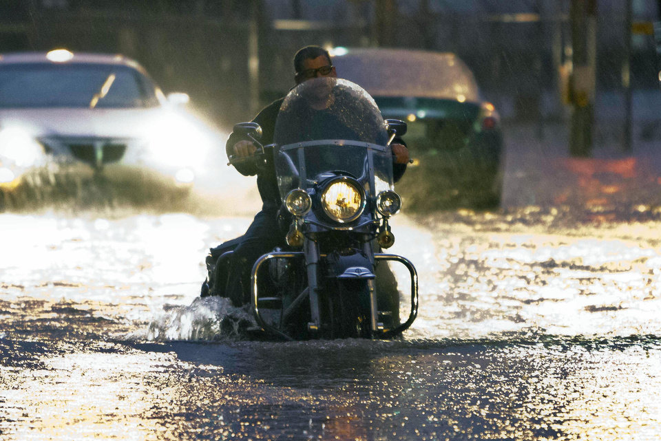 Photo - A man on a motorcycle drives through flood water on Western Ave. at NW 5th Street in Oklahoma City on Friday, May 31, 2013. (AP Photo/Alonzo Adams)