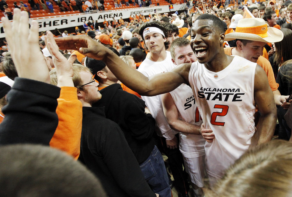 Photo - OSU's Obi Muonelo (2) celebrates with fans in front of teammate Keiton Page (12) after the men's college basketball game between the University of Kansas (KU) and Oklahoma State University (OSU) at Gallagher-Iba Arena in Stillwater, Okla., Saturday, Feb. 27, 2010. OSU won, 85-77. Photo by Nate Billings, The Oklahoman