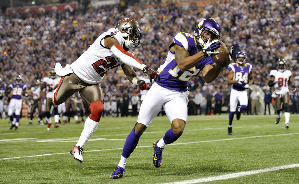 Photo -   Minnesota Vikings wide receiver Percy Harvin, right, catches an 18-yard touchdown pass ahead of Tampa Bay Buccaneers cornerback Eric Wright, left, during the first half of an NFL football game Thursday, Oct. 25, 2012, in Minneapolis. (AP Photo/Jim Mone)
