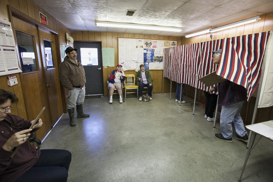 Photo -   Vernon Straw emerges from behind the curtain of a voting booth at the fire hall in Dunbar, Neb., Tuesday, Nov. 6, 2012, to a waiting Terry Petersen, left. The village fire hall was too small to place cardboard voting stations, so election officials had to bring back the old style curtained voting booths. (AP Photo/Nati Harnik)