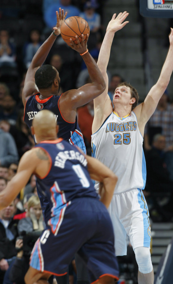 Photo - Charlotte Bobcats center Al Jefferson, back left, puts up shot over Denver Nuggets center Timofey Mozgov, back right, of Russia, for basket to give the Bobcats a three-point lead with 23 seconds remaining in the fourth quarter of the Bobcats' 101-98 victory in an NBA basketball game in Denver on Wednesday, Jan. 29, 2014. Bobcats guard Gerald Henderson, front, looks on. (AP Photo/David Zalubowski)