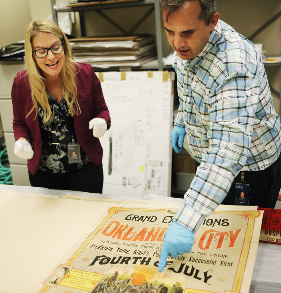 Photo - Nicole Harvey, Oklahoma Historical Society executive assistant (left), and Chad Williams, the Oklahoma Historical Society Director of Research, talk about details on a poster from the 1889 4th of July celebration in Oklahoma City. The poster will be displayed in an exhibit in July 2013 after it was preserved in a time capsule buried in 1913 that was unearthed earlier this year. July 1, 2013 Photo by KT KING, The Oklahoman