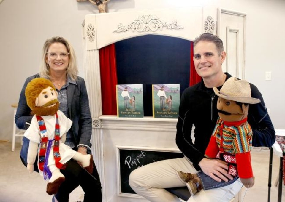 Photo -  Susan Rother Bond and her husband James Bond pose with puppets based on her children's book