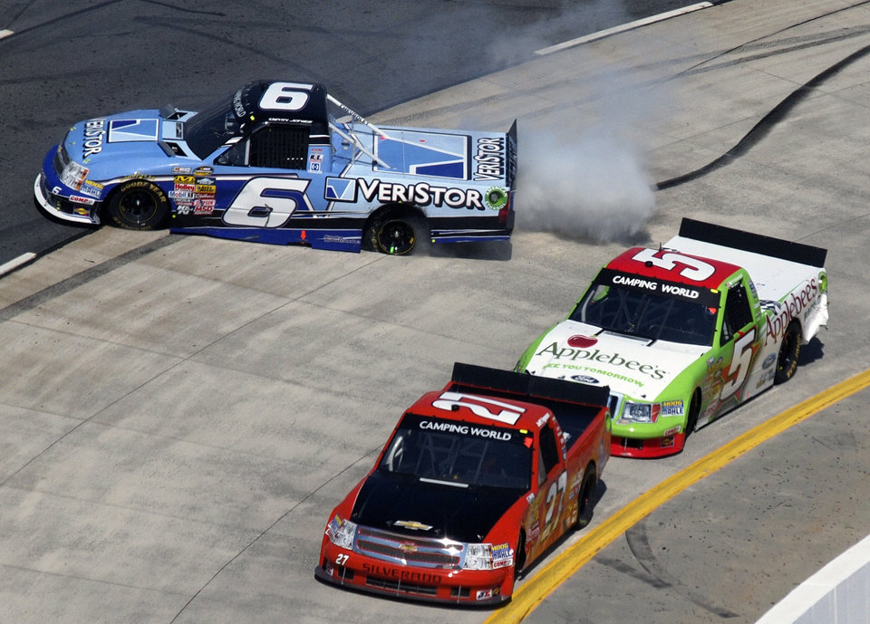 Driver Devin Jones (6) spins out as Jeff Agnew (27) and Tim George Jr. (5) pass by during the Kroger 250 NASCAR Truck series auto race at Martinsville Speedway in Martinsville, Va., Saturday, April 6, 2013. (AP Photo/Steve Sheppard)