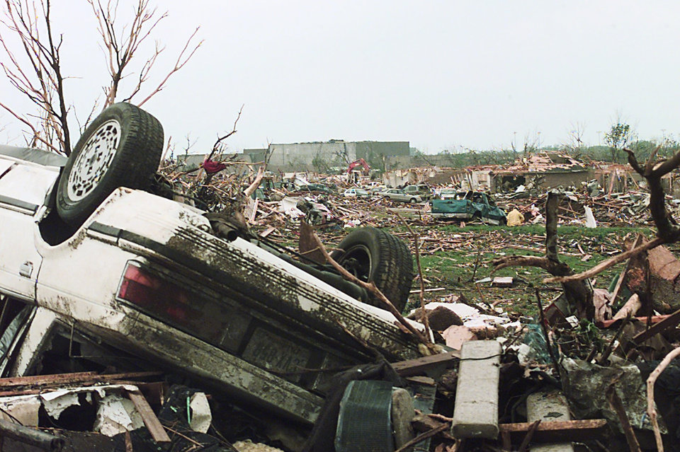 MAY 3, 1999 TORNADO: TORNADO DAMAGE: A CAR LAYS UPSIDE DOWN WHILE AN APARTMENT COMPLEX IS FLATTENED IN THE BACKGROUND AND BEYOND THAT SITS WESTMOORE HIGH SCHOOL OFF OF WESTERN AND 12TH STREET IN MOORE, OK.