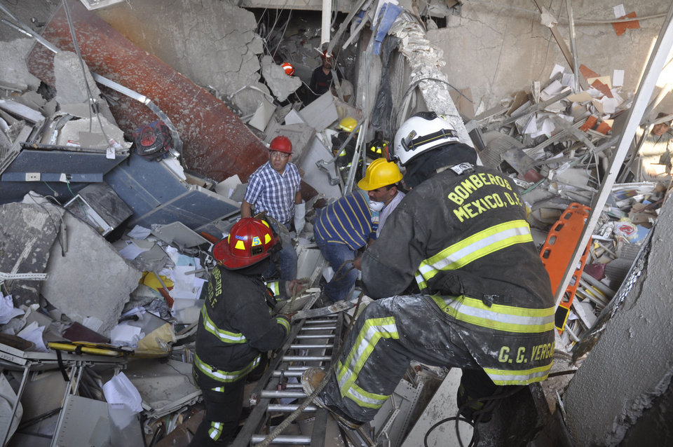 Photo - Firefighters belonging to the Tacubaya sector and workers dig for survivors after an explosion at an adjacent building to the executive tower of Mexico's state-owned oil company PEMEX, in Mexico City, Thursday Jan. 31, 2013. A large explosion occurred in the lower floors of the building and dozens have been reported injured so far. (AP Photo/Guillermo Gutierrez)